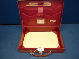 A red leather briefcase with calendar, pencil and key.