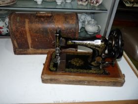 A Singer sewing machine in black and gold in wooden case.