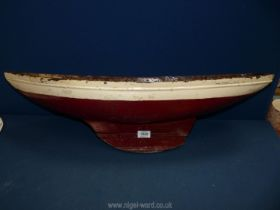 """A hand carved red and white model boat, 30"""" long x 8"""" wide."""
