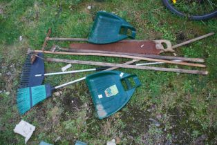 Garden tools including saw, broom and leaf grabbers.