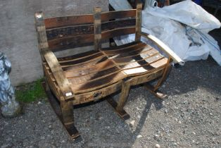 A double seated garden rocking seat made from old whisky barrels.