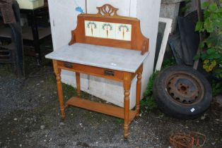 Marble topped washstand with tiled back.
