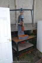 A screw action press with a dolly on a stand.