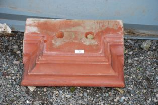 A terracotta finished plinth.