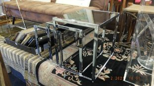 A chrome/ black glass nest of three tables