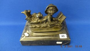 A bronze of a boy reading a book,