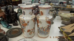 A pair of orange and white vases