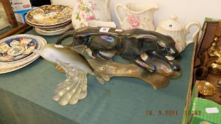 A figure of a Jaguar and a glass figure of a Dolphin