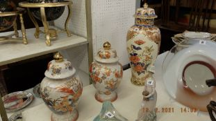A pair of Orange and white temple jars plus a larger lidded temple jar