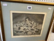 A framed etching of a child with toys dated 86