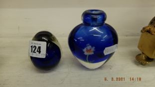 A blue paperweight and a blue floral vase