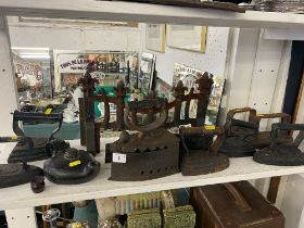 A qty of antique flat irons and a fire grate