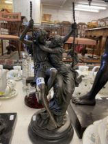 A Bronze man and a lady on swing