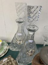 A pair of cut glass decanters with Crown Derby labels