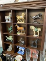 A collection of 12 Horse figures with display cabinet