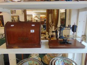 A vintage lead miniature sewing machine in wooden case