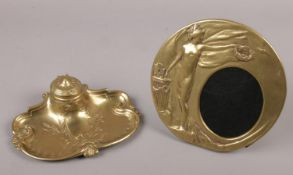 An art nouveau brass picture frame along with a brass ornate art nouveau inkwell. Plastic liner in
