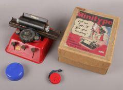 A vintage metal child's Minitype typewriter in original box.