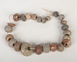 A collection of 18th century saltglazed stoneware spinning weights strung in graduated formation,