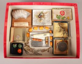 A box of collectables. Including pen knives, Androgynoceras ammonite fossil, dinosaur charm, etc.