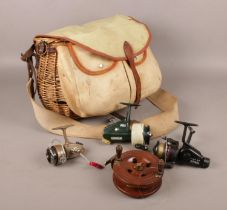 A wicker and canvas fishing creel with contents of four fishing reels. Includes Abu Cardinal 66,