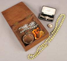 An oak box of costume jewellery. Including white paste stone set cocktail watch, earrings, vintage