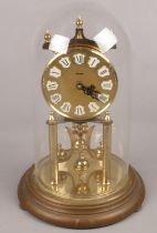A brass Kundo torsion clock with gilt dial under glass dome.