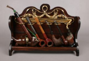 A wooden pipe rack with six wooden pipes - to include a German Bruyere pipe with metal flip top,