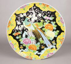 A Japanese polychrome charger decorated on a blackground with a pair of phoenix and peonies,