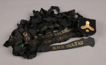 A collection of Royal Navy Cap Tallies. H.M.S Sultan, H.M.S Raleigh, H.M.S Caledonia examples etc