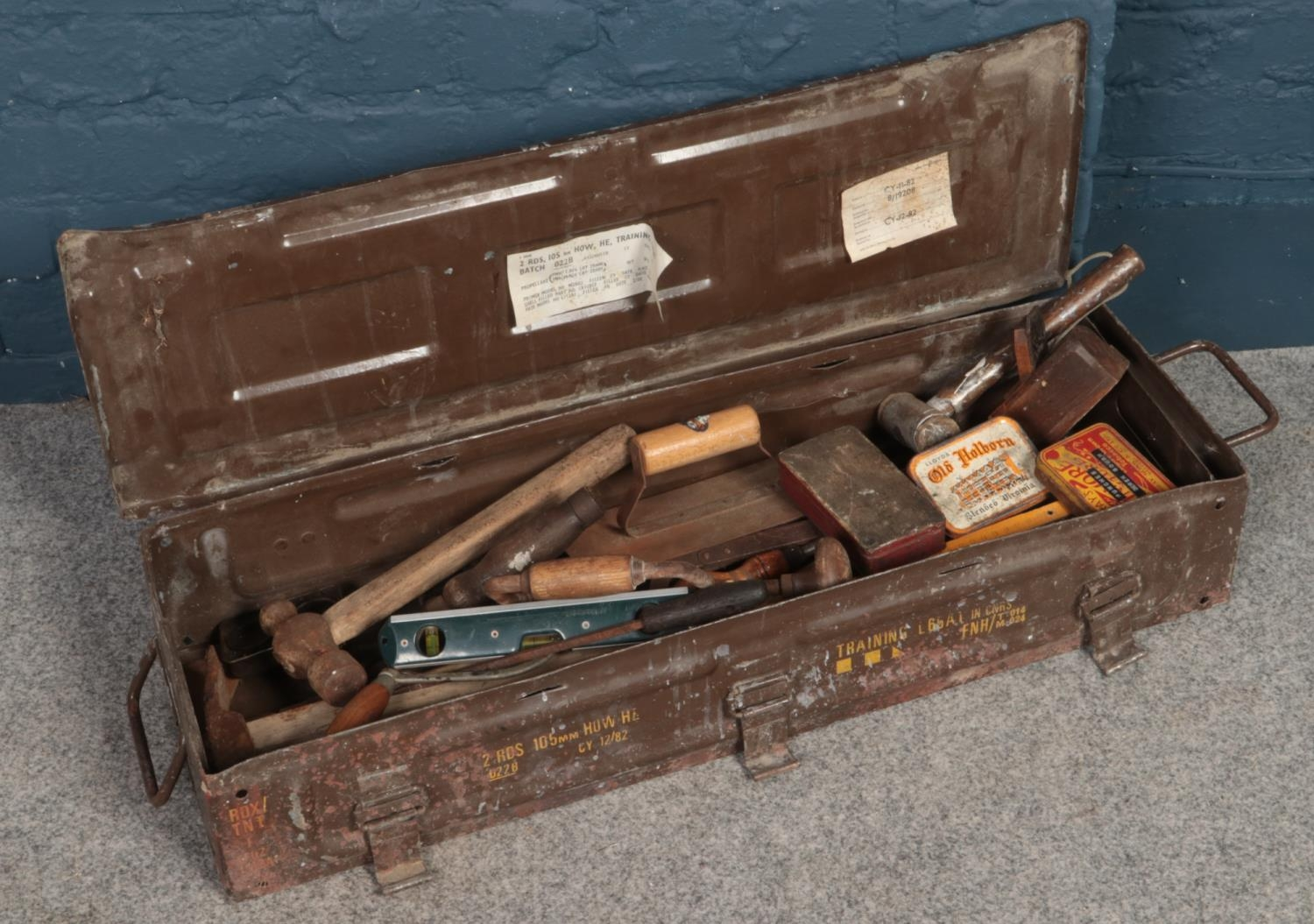 A metal tool case of vintage hand tools. Including hammers, saws, hand crack screwdrivers, wood