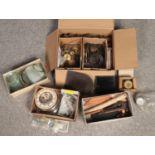 A box of various clock spares. Includes glasses, bells, coils, dials etc.