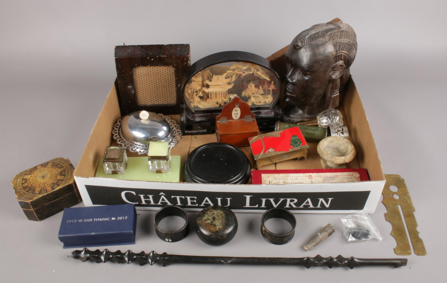 A box of collectables. Includes carved wooden bust, cork display, oriental napkin rings etc.