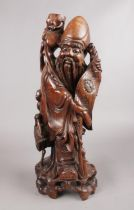 A hardwood oriental carved figure depicting a sage figure with scroll. This figure has ivory