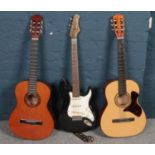 Two acoustic guitars along with a Stratocaster style electric guitar.