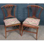 A pair of Edwardian inlaid mahogany pierced back nursing chairs.