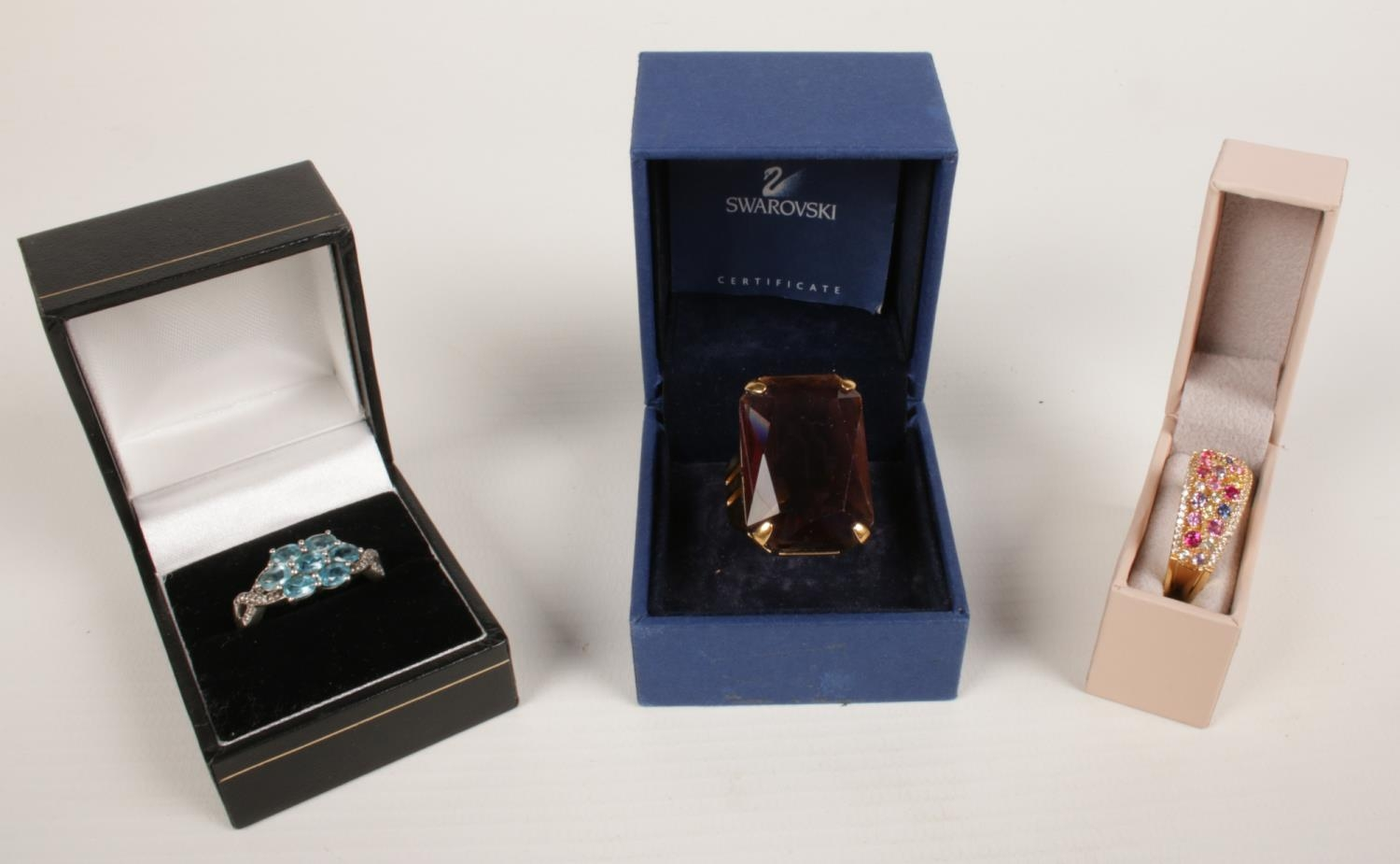 A Swarovski dress ring set with large purple stone along with two other dress rings.