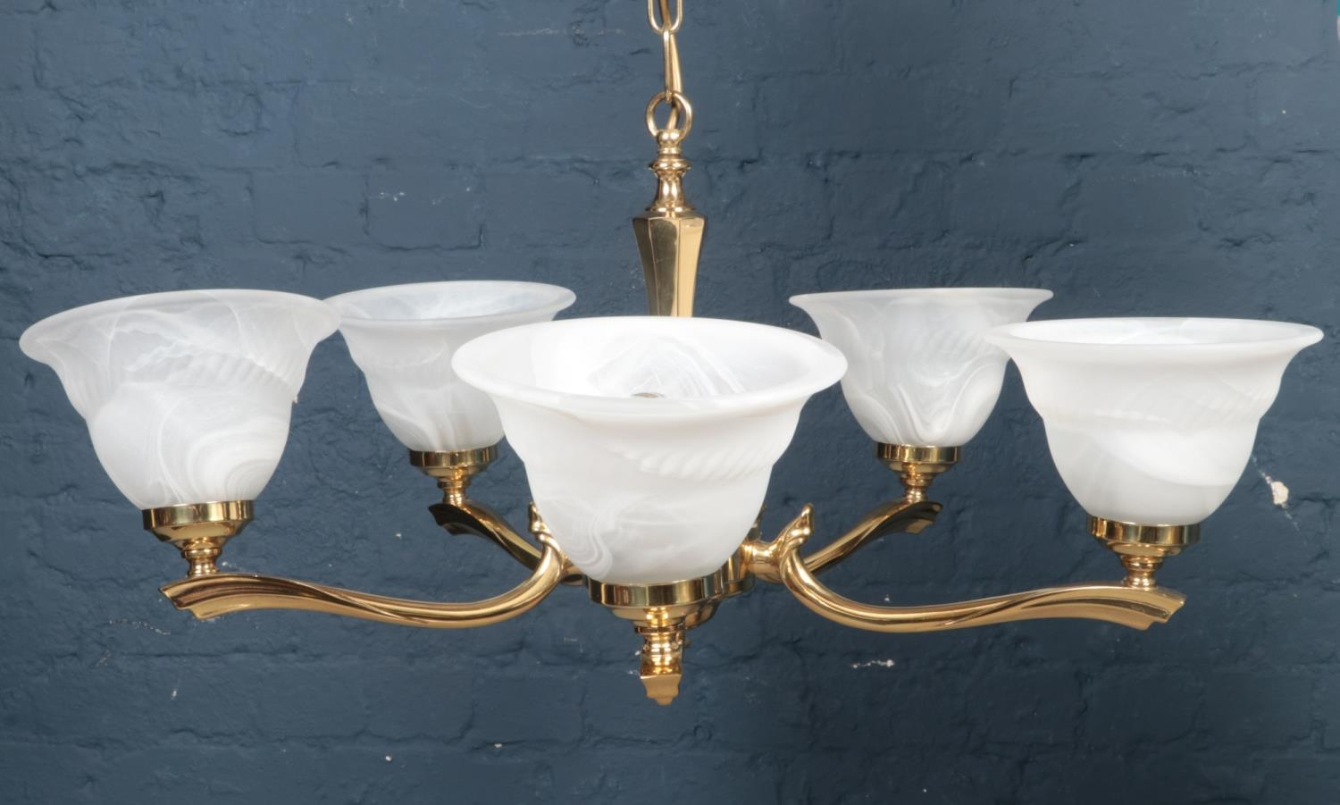 A 5 arm brass chandelier with glass bowl shades.
