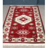An Aztec style wool & silk rug in red, cream and pale green. H:205cm, W: 128.5cm. Condition good.