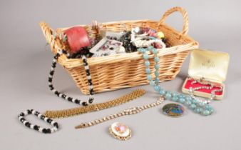 A basket of costume jewellery. Beads, Necklaces, brooches examples etc.