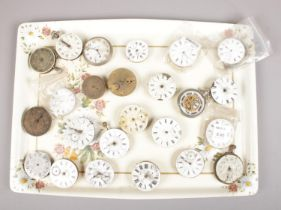A tray of pocket watch movements, mostly with enamel dials.
