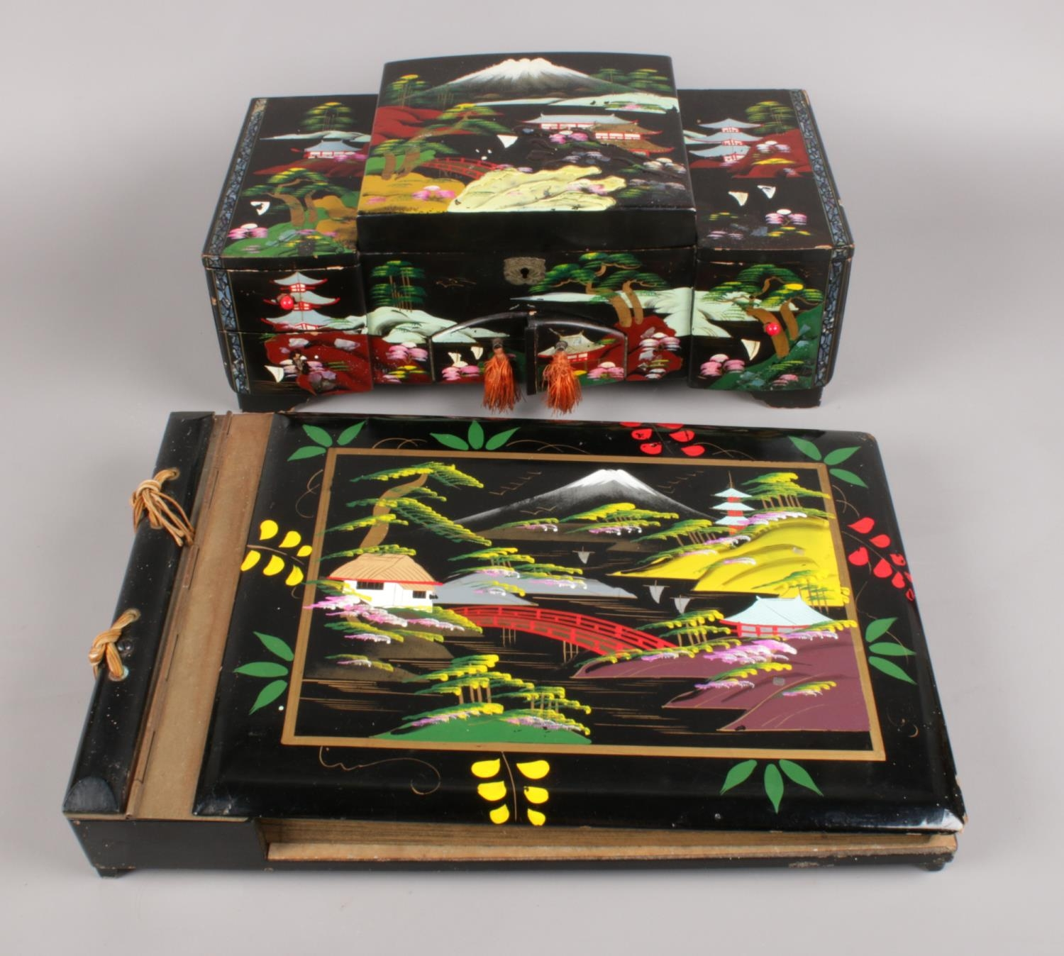 A Japanned musical jewellery box and matching album.