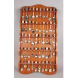An oak display rack with contents of collectors spoons. Some spoons with enamel decoration. (