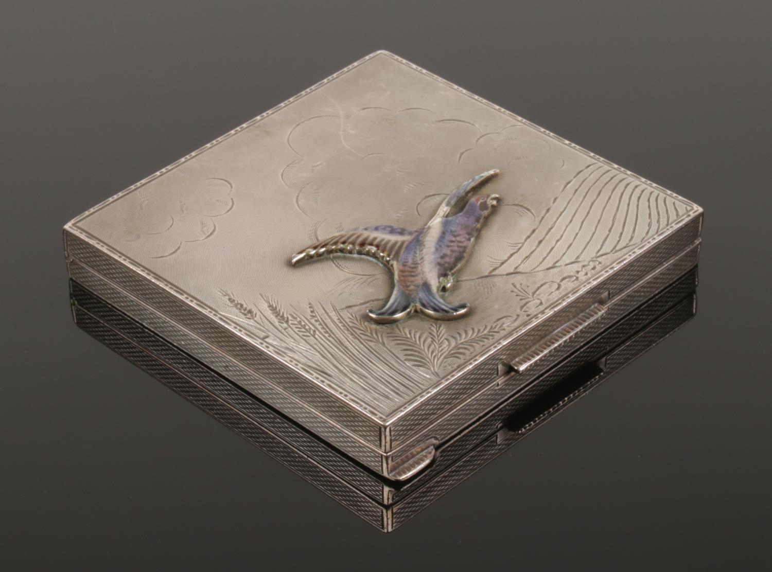 A George VI silver powder compact. With engraved decoration and applied enamel grouse. Assayed