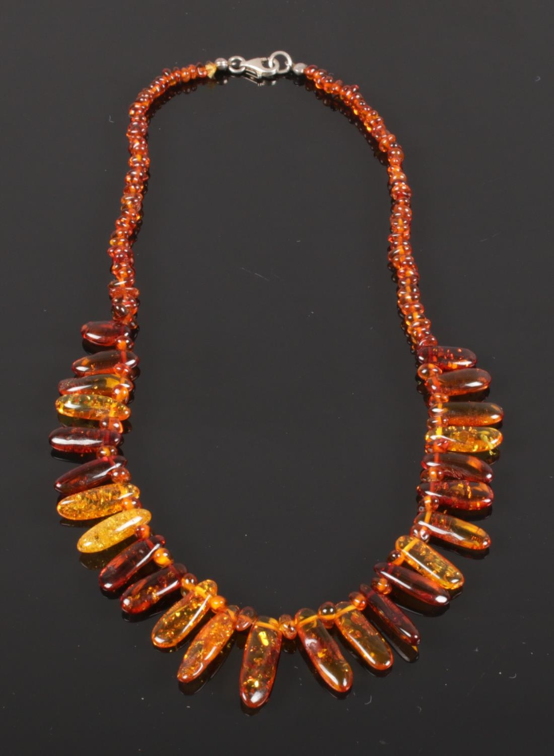 A cased cognac amber necklace comprising approximately 150 shaped and graduated beads with safe lock