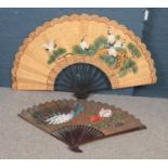 Two large hand painted oriental fans. One decorated with cranes, the other with peacocks. (Largest