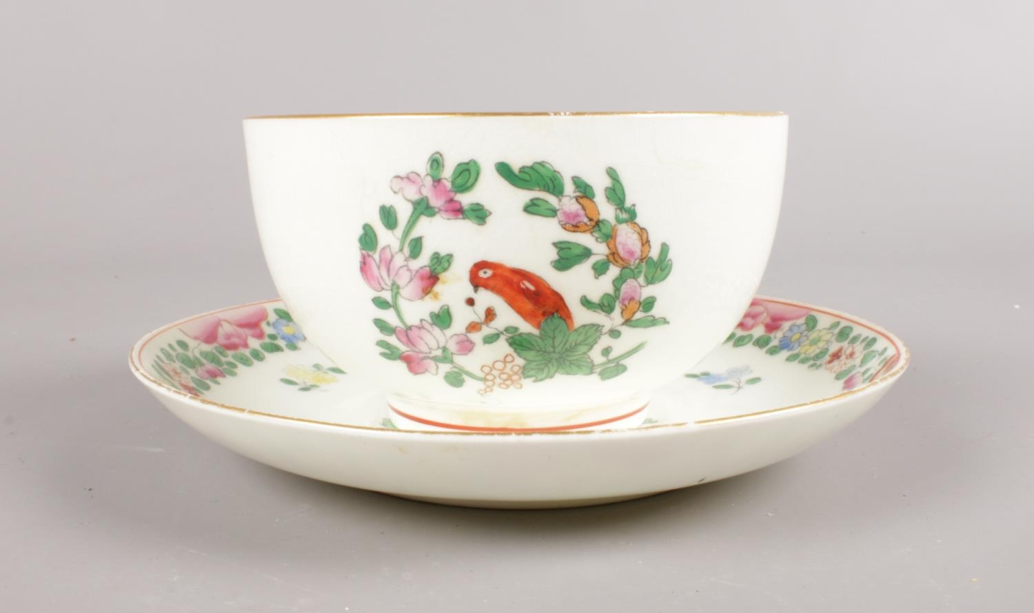 A Royal Worcester hand-painted small bowl and saucer. Decorated in the Worcester parrot pattern with