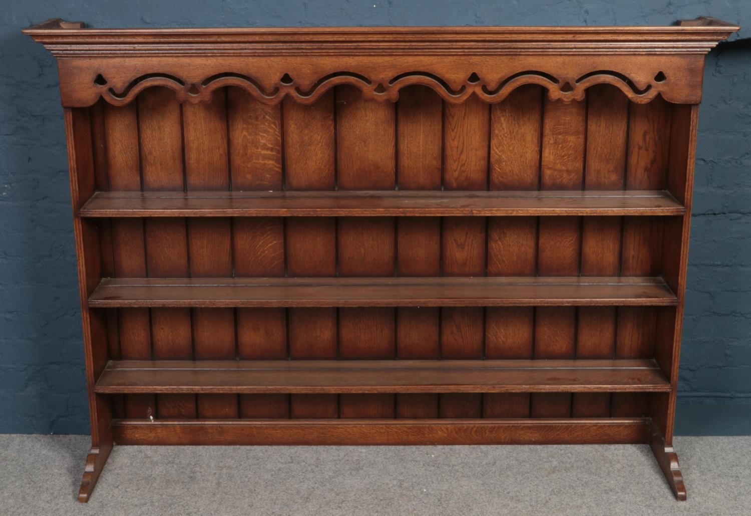 A large carved oak dresser top fitted with three shelves. (H130cm x W183cm x D38cm)