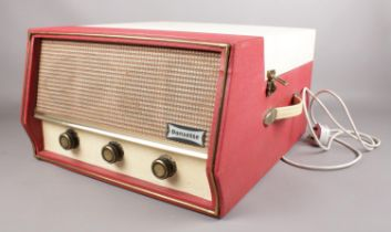 A Dansette 'Conquest Auto' portable record player (missing legs) in red and cream. H:25.5cm, W: 40.