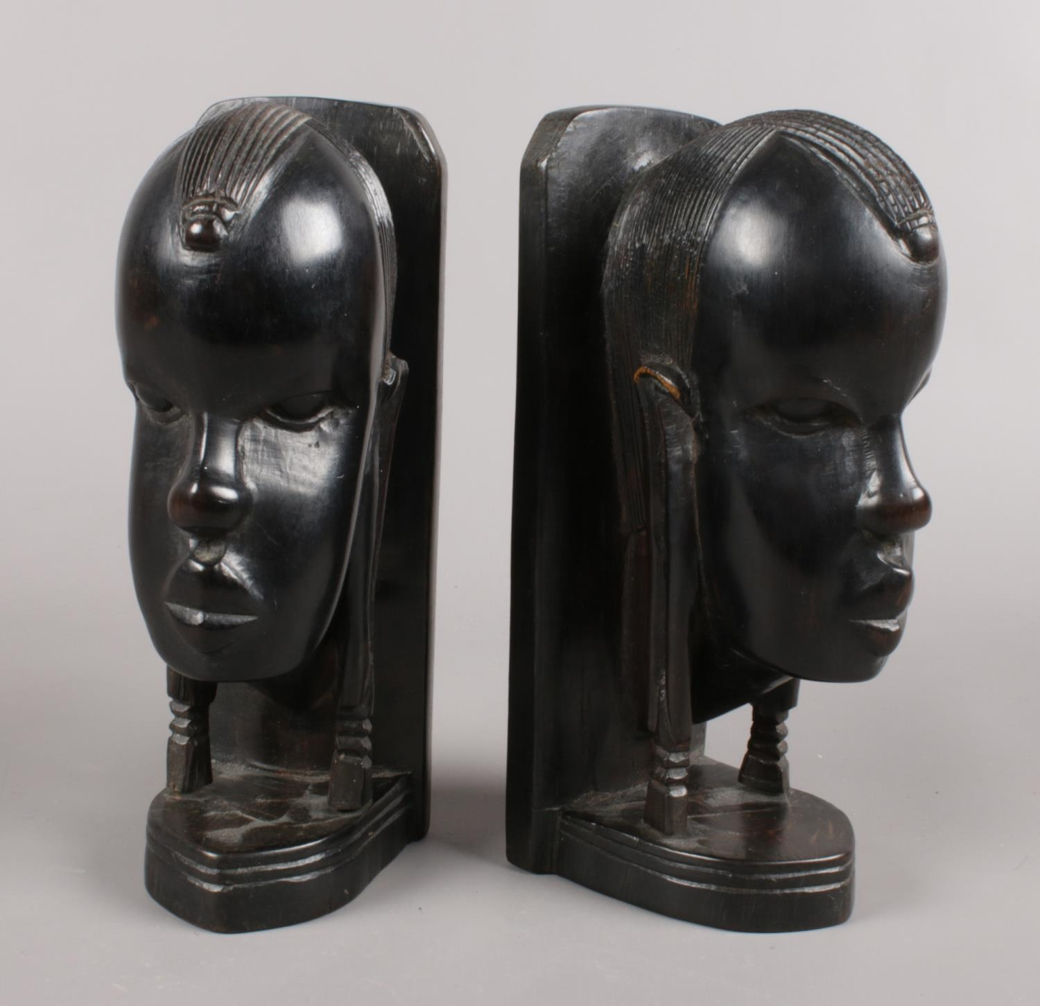 A pair of carved and ebonised book ends. African tribal busts.